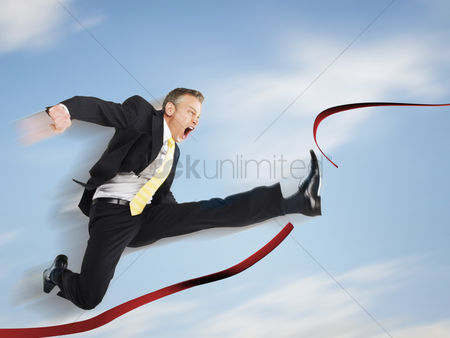 Rage : Business man jumping through red tape digital composite