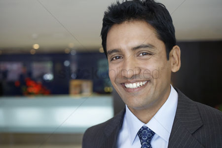 Smile : Business man standing in hotel lobby portrait close up