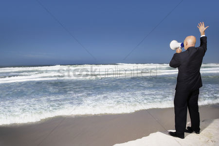 Bald : Business man standing on edge of sea using megaphone back view