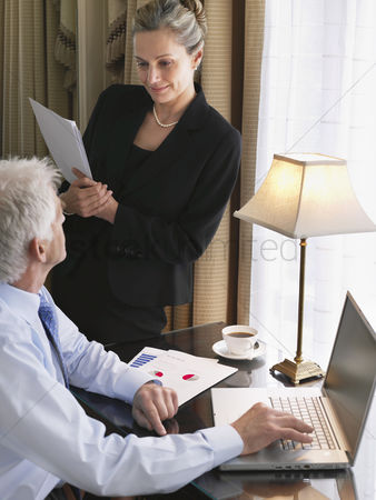 Sitting on lap : Business man using laptop business woman sitting on desk reading documents elevated view