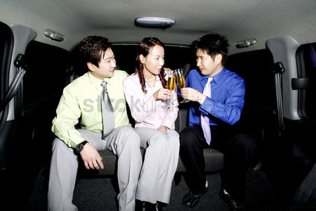 Celebrating : Business people drinking wine in the car