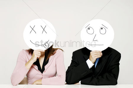 Conceptual : Business people holding cardboard cutout with facial expression