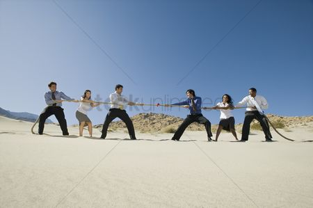 Rope : Business people playing tug of war in the desert