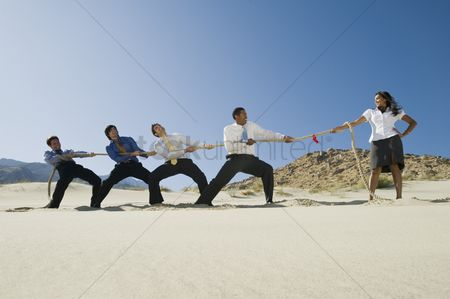 Asian : Business people playing tug of war in the desert