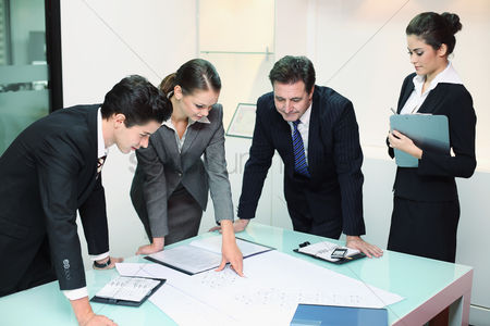 Smiling : Business people reviewing blueprints together