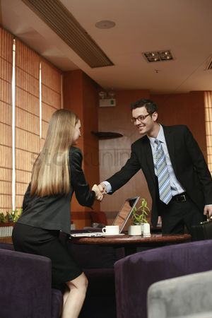 Eastern european ethnicity : Business people shaking hands in a cafe