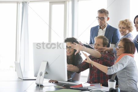 Three quarter length : Business people using computer in office