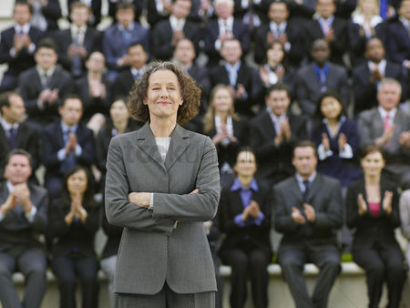 Curly hair : Business woman standing in front of business people sitting in bleachers clapping portrait