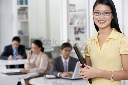 Black background : Business woman standing in office colleagues in background portrait