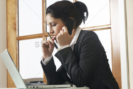 Biting finger : Business woman using mobile phone at desk in office