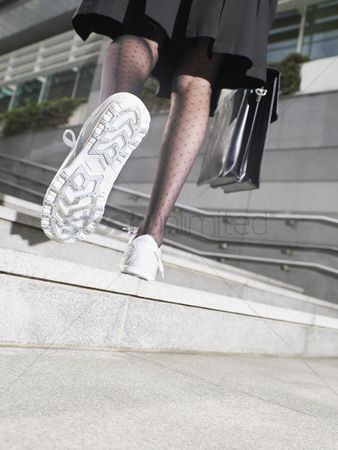 Steps : Business woman wearing running shoes walking up steps low section low angle view back view