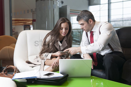 Employee : Businessman and businesswoman at meeting with laptop and tablet