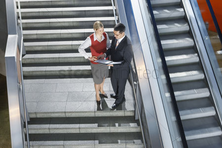 Stairs : Businessman and businesswoman conversing on stairs elevated view