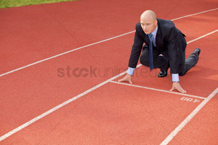 Bald : Businessman at the start line of running track