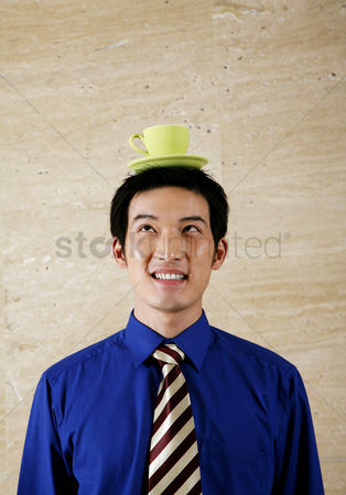 Careful : Businessman balancing cup on his head