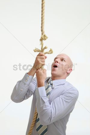 Rope : Businessman climbing up a fraying rope