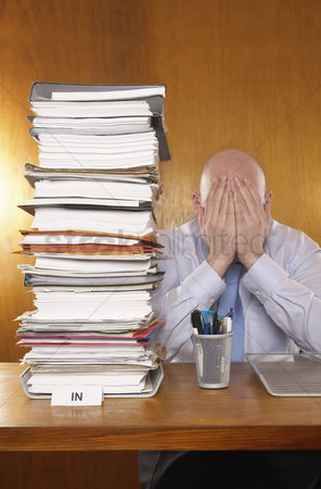 Bald : Businessman covering face with hands next to stack of paperwork at desk