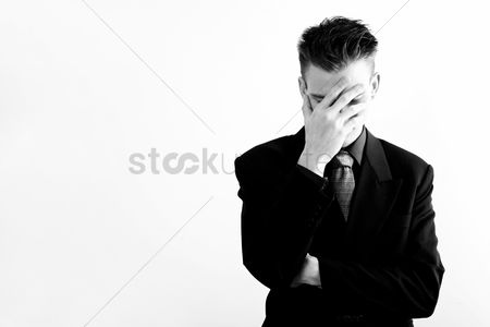 Business suit : Businessman covering his face with his hand