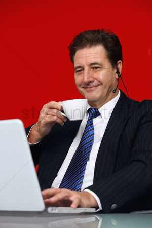40 44 years : Businessman drinking coffee while video conferencing on laptop