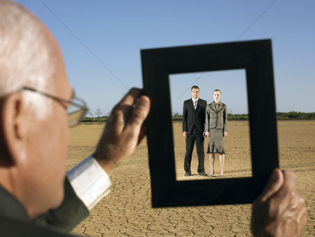 Land : Businessman framing couple in desert