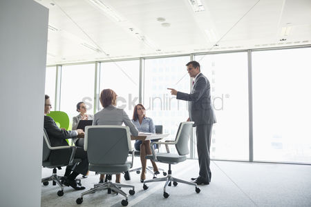 Gesturing : Businessman giving presentation in conference room