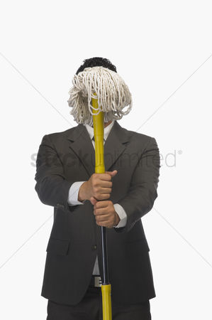 Obsessive : Businessman holding a broom in front of his face