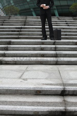 Staircase : Businessman holding a cup of coffee  standing on stairs
