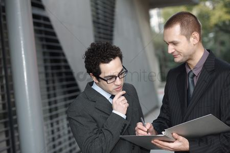 Advice : Businessman holding document and pen  another businessman reading the document