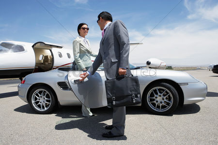 Two people : Businessman holding door of convertible for colleague on landing strip near private jet