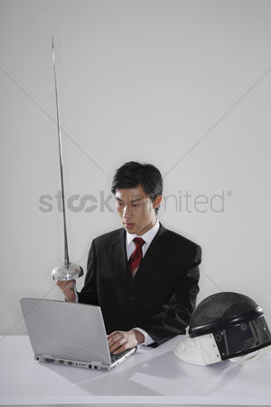 Fight : Businessman holding fencing foil while using the laptop