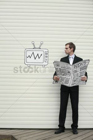 Cardboard cutout : Businessman holding newspaper and looking at televesion