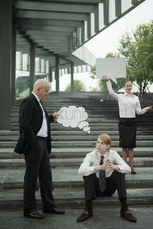 Cardboard cutout : Businessman holding thinking bubble above another businessman s head  businesswoman holding speech bubble
