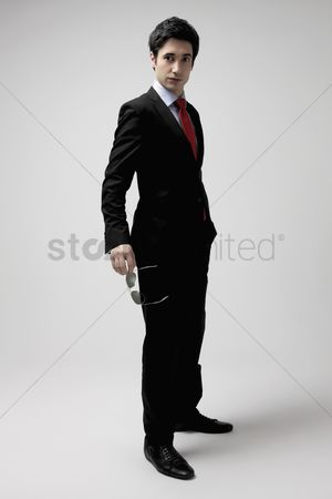 Man suit fashion : Businessman in full suit holding sunglasses