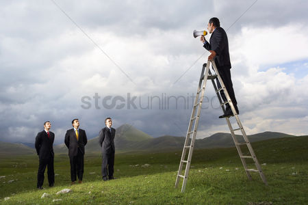 Leadership : Businessman in mountain field speaking through megaphone to other businessmen full length