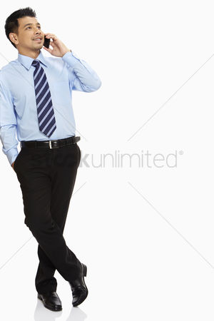 Portability : Businessman leaning against a wall  talking on mobile phone