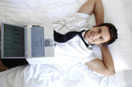 Internet : Businessman listening to music on his earphones while using laptop