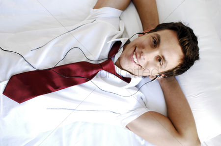 Relaxing : Businessman listening to music through earphones