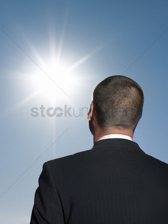 Motivation business : Businessman looking at sun head and shoulders back view