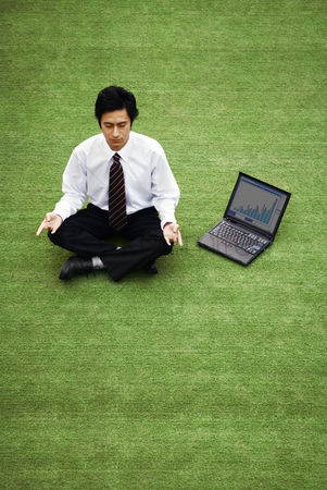 Practising yoga : Businessman meditating on the field