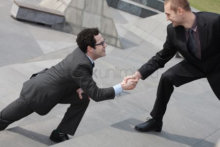 Motivation business : Businessman offering outstretched hand to another businessman