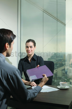 Assistance : Businessman passing folder to businesswoman