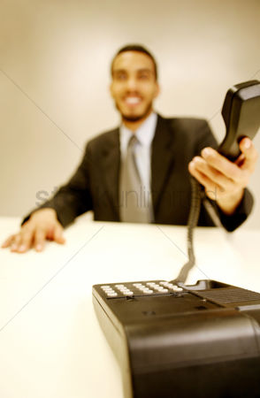 Answering calls : Businessman picking up a phone call