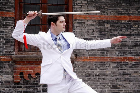 Motivation business : Businessman practicing kung fu with a chinese sword