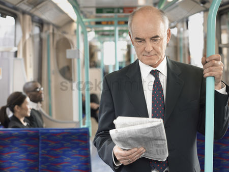 Interior background : Businessman reading newspaper on train holding onto bar
