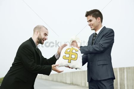 Motivation business : Businessman receiving a bag of money from another businessman