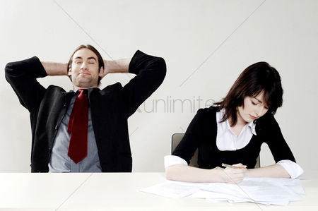 Pressure : Businessman relaxing while his colleague is doing her work