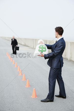 Motivation business : Businessman running in between traffic cones  another businessman holding a bag of money