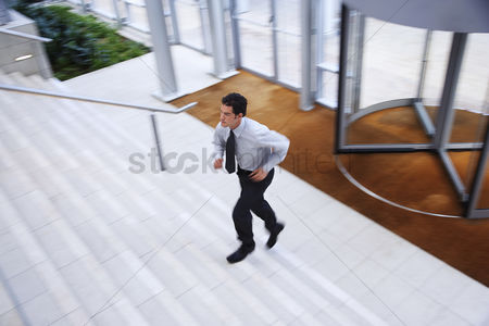 Steps : Businessman running up stairs in office lobby