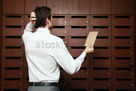 Wondering : Businessman scratching his head while looking at mail slots