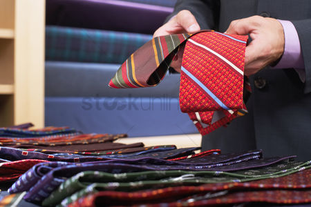 Selection : Businessman selecting ties in clothes store mid section